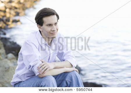 Teenage Boy Sitting By Water