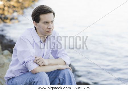 Teenage Boy Sitting On Rocks