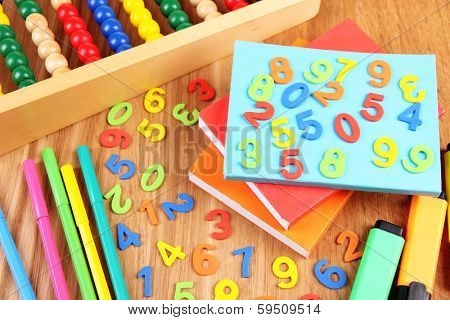 Colorful numbers, abacus, books and markers on wooden background