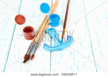 Hand made ceramic anchor and color paints on wooden table