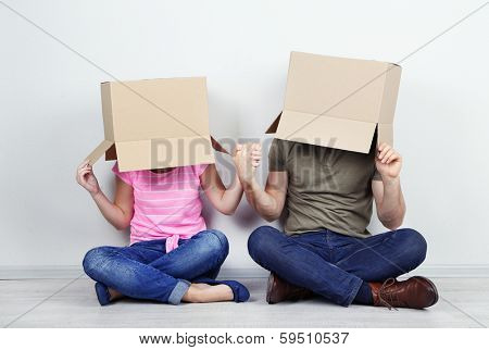 Couple with cardboard boxes on their heads sitting on floor near wall