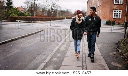 Young Couple Walking On A Sidewalk