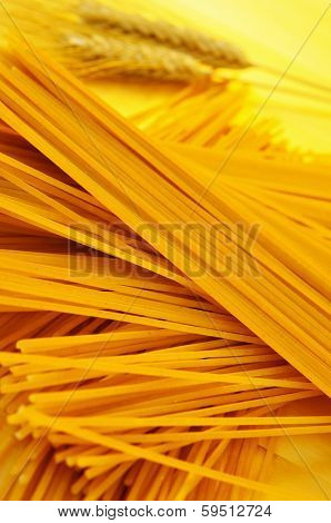 a pile of uncooked spaghetti and some wheat ears on a wooden worktop