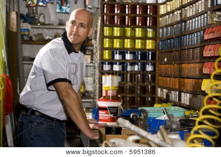 Man working in print shop by shelves stacked with inks