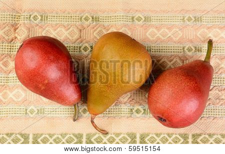 High angle closeup shot of a group of three pears on a table cloth. Bosc and Red Pears are shown.
