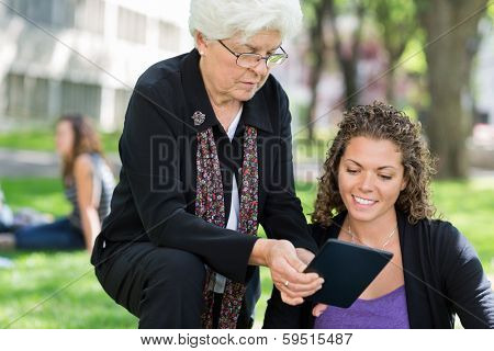 University professor helping grad student using digital tablet