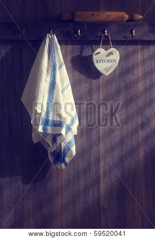 Kitchen teatowels hanging on wall with sunrays filtering through