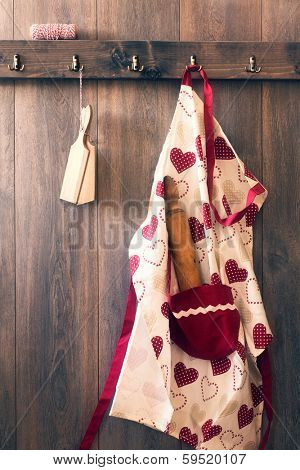 Cooks apron with rolling pin and butter pats hanging on hooks in the kitchen - vintage tone effect