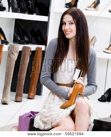 Woman keeps shoes and credit card in the footwear shop where she would like to buy new pumps