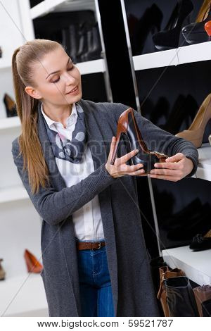 Woman with shoe in hand chooses heeled shoes looking at the shelves with numerous pumps