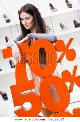 Woman showing the percentage of sales on stylish shoes in the shopping center against the window case with pumps