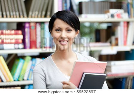 Student with book against bookshelves at the library. Knowledge and self-development