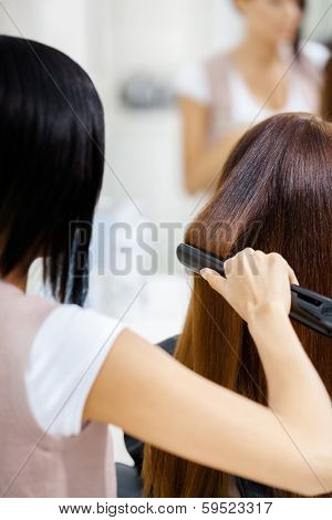 Backview of hairdresser doing hair style for woman in hairdressing salon. Concept of fashion and beauty