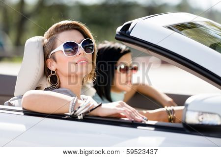 Close up of girls wearing sunglasses in the cabriolet. Little holiday trip of friends