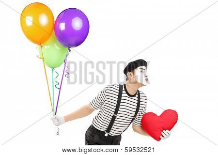 Young mime artist with balloons and red heart giving kisses isolated on white background
