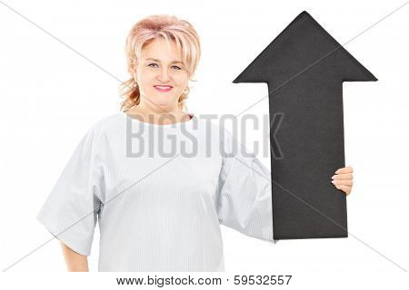 Female patient in hospital gown holding big black arrow pointing up isolated on white background