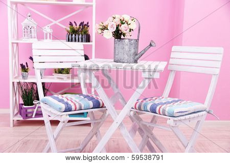 Garden chairs and table with flowers on shelves on pink background