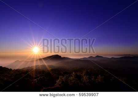 Sunrise above foggy mountain