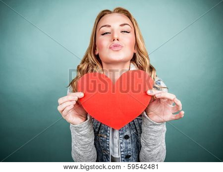Portrait of cute teen girl with red paper heart isolated on gray background, kiss with love, Valentine day, affection concept