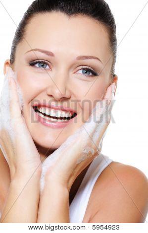Riendo a feliz hermosa mujer limpiar su cara