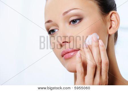 Mujer cuidando de su cara con crema hidratante