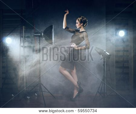Young and emotional woman in fashion dress over glamour background (photo studio backstage)