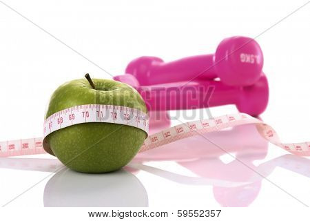 Diet diabetes weight loss concept with tape measure organic green apple and pink dumbbels on a white background.
