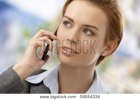 Closeup portrait of beautiful young businesswoman talking on mobilephone, looking away.