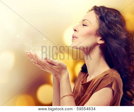 Beauty Young Woman Blowing Magic Dust with stars from her Hands. Holiday Concept. Beautiful Girl. Miracle.