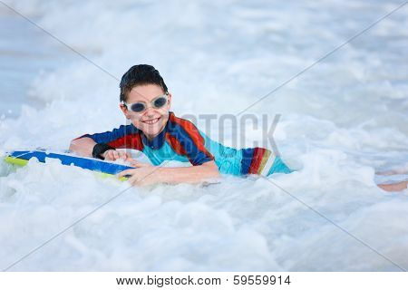 Little boy on vacation having fun swimming on boogie board