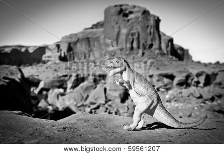 Black and white picture with a dinosaur and Monument Valley in background