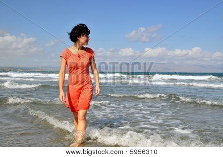 Woman Walking In Water Looking Aside
