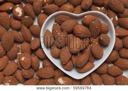 Almond nuts, healthy food ingredient in heart shape tray