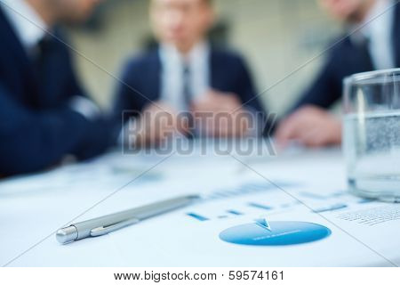 Image of business document and pen at workplace with group of colleagues interacting on background