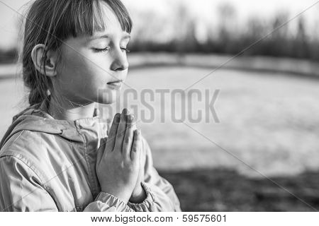 Young girl praying on the background of nature