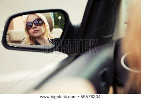 Blond woman looking in the car mirror