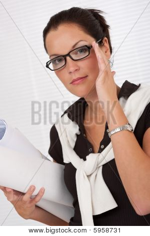Female Architect Holding Plans And Glasses
