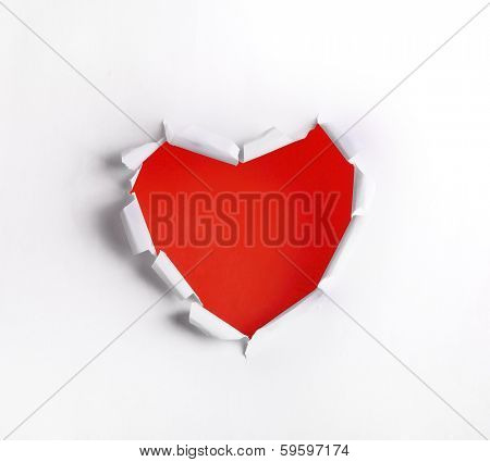 Heart shaped hole in white paper with red blank space