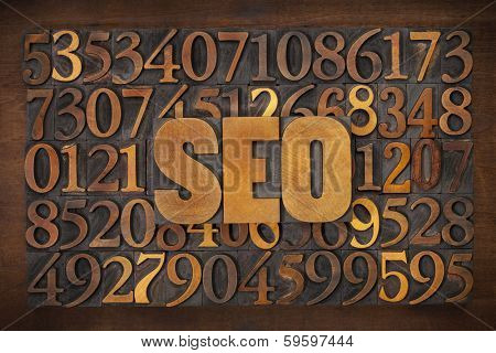 SEO (search engine optimization) acronym - letterpress wood type text against number background