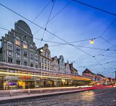 AUGSBURG, GERMANY - SEPTEMBER 29, 2013: Light trails remain as a street car passes cafes and shops i