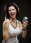Half-length portrait of female rock singer with microphone. Concept of rock music and rave
