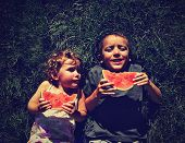 stock photo of eat grass  - two kids eating watermelon done with a retro vintage instagram filter - JPG