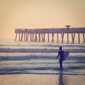 stock photo of early morning  - Surfing at the pier in the early morning with retro effect - JPG