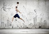 Young man throwing ball into basket in jump