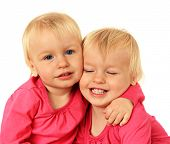 stock photo of identical twin girls  - Cute two year old identical twin girls hugging - JPG