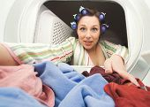 picture of lint  - a woman reaching in the dryer for clothes - JPG