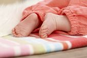 Closeup photo of bare baby feet lying on blanket.
