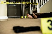 foto of crime scene  - a body on the ground of a crime scene with a gun in the foreground - JPG