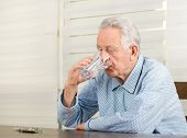 stock photo of blisters  - Old man in pajamas drinking glass of water and have pills blister on table - JPG