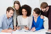 picture of enthusiastic  - Teamwork at the office with a group of enthusiastic smiling young business people clustered around a pretty African American woman holding a tablet computer - JPG